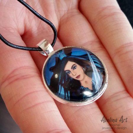 Queen of Swords art pendant held by model