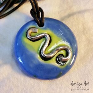 Silver Snake symbol pendant on blue and yellow background