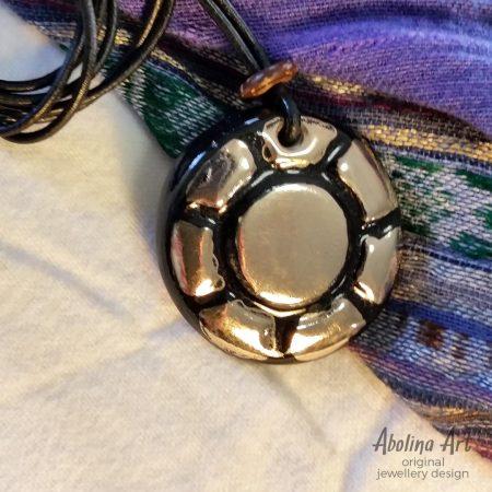 Sunray pendant - platinum lustre strung on leather cord