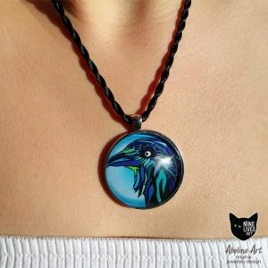Model wearing Blue Raven art pendant set in 40mm glass cabochon on antique silver metal back